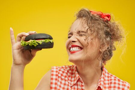 Portrait of smiling cheerful blonde girl with closed eyes and red lips holding tasty black burger with yellow background behind. Attractive female model with curly hair enjoying fast food meal