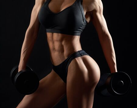 Healthy, sexy female muscular body with beautiful, pumping muscles and buttocks. Young woman in black sportswear posing with dumbbells on black background.