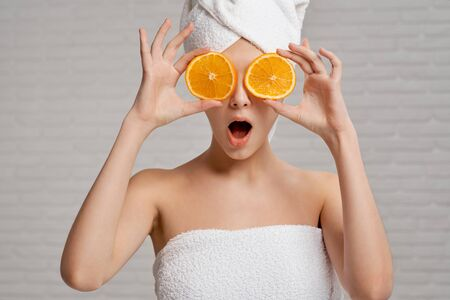 Pretty, cute girl making binoculars with two pieces of orange, closing eyes. Beautiful, young woman with perfect skin posing at camera. Model with bare shoulders in white towel on head and body. Banco de Imagens