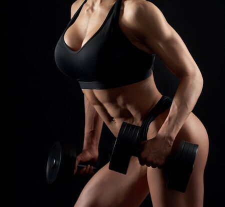 Attractive, sexy, female, muscular body in black sportswear on black background. Young, strong woman in black sportswear training with dumbbells, posing in studio side view.