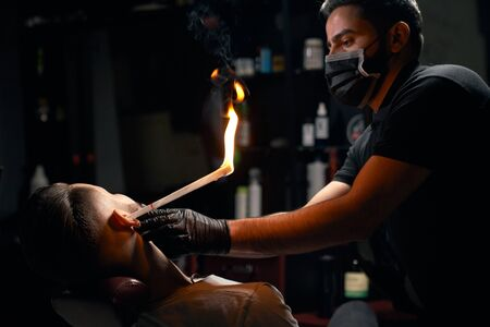 Portrait of confident male barber in black shirt, wearing mask on his mouth and gloves on hands, trying to put burning twisted paper into clients ear.Concept of professional hair removal from ears Banco de Imagens