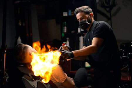 Portrait of professional barber in black skirt, gloves and mask on his mouth giving hair fire treatment to bearded male customer.Handsome hairdresser using extreme technology for hair removal Banco de Imagens