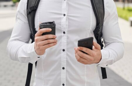 Cropped close up of man with backpack behind shoulder, wearing in white shirt holding black phone and black coffee cup. Archivio Fotografico