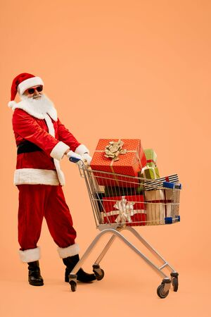 Mature Father Christmas in traditional costume and red sunglasses standing in studio with orange background with shopping trolley full of presents. Happy Santa Claus giving gifts at Christmas.