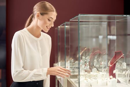 Beautiful lady with blond hair and tied knot in white silk blouse smiling and looking at showcase with luxury jewelry in store. Female assistant controling the appropriate look of precious metal. Reklamní fotografie - 135500196