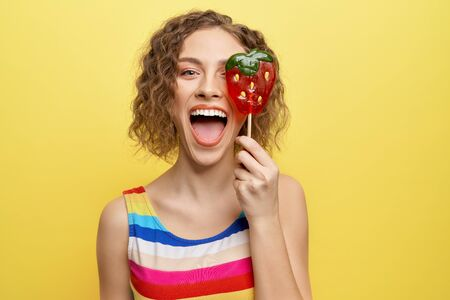 Happy, cheerful girl holding sweet red strawberry lollipop and having fun. Playful model in striped dress looking at camera, posing on yellow background. Foto de archivo