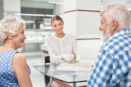 Happy senior romantic couple looking on each other while choosing wedding rings at luxury jewelry market. Professional friendly jeweller helping her customers to buy rings Stock Photo