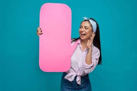 Beautiful, playful girl posing with pink paper speech bubble, smiling. Happy, positive model wearing in pink shirt, blue headband and jeans skirt having perfect straight black hair. Banque d'images - 135500433