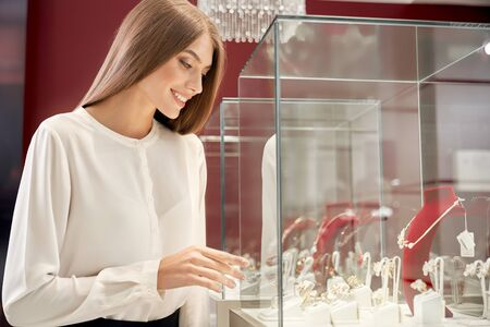 Beautiful smiling girl with long straight hair wearing white silk blouse looking at window case with shining luxury jewelry. Young attractive lady shopping in jewelry store