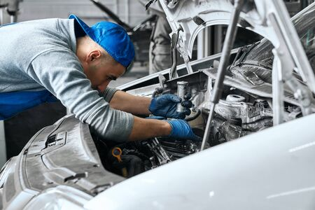 Male car operator wearing blue overalls,cap and gloves working under the hood of white car and checking attentively serviceability of engine at repair garage. Concept of car maintenance Stock Photo