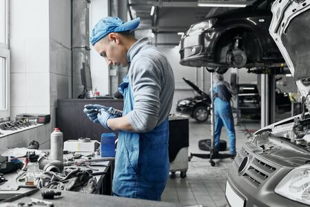 Young auto mechanic in blue and dirty overalls working near black car with opened hood is going to change old spark plugs in car engine. Qualified repairman fixing vehicles motor in service station