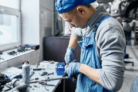 Repairman in car service wearing blue uniform and protective rubber gloves working near table with a lot of tools on it,preparing details to replace them in disassembled auto.Working process concept