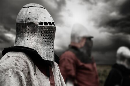 Side view of medieval knight in iron helmet posing. Selective focus of brave man standing outdoors while sky is cloudy, other warriors behind. Concept of warrior, middle ages.