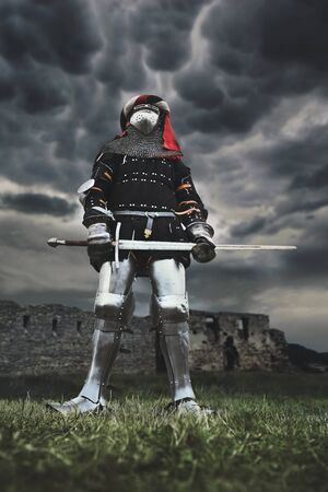 From below view of medieval knight in iron armor posing and holding big sword. Portrait of brave man standing outdoors. Ruins on backgroung and cloudy sky. Concept of warrior, middle ages.