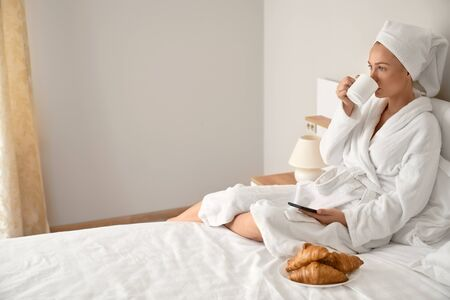 Side view of young woman wrapped in towel and bathrobe waking up in morning using phone on bed. Pretty female drinking coffee and posing in bedroom. Concept of gadgets and social networks.