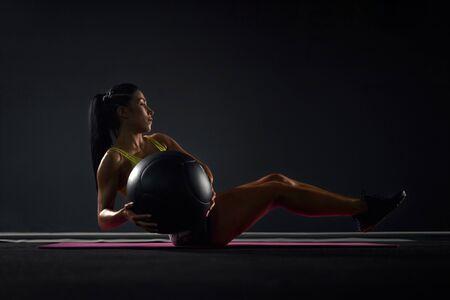Vue latérale du bodybuilder féminin fort en vêtements de sport faisant des exercices avec ballon dans la salle de gym. Femme musclée aux cheveux noirs formation abs sur tapis rose dans une atmosphère sombre. Concept de sport, musculation. Banque d'images