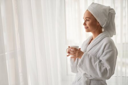 Side view of young smiling girl in towel and bathrobe holding cup of hot drink. Crop portrait of pretty female enjoying morning breakfast, standing and looking out window. Concept of lifestyle, relax.