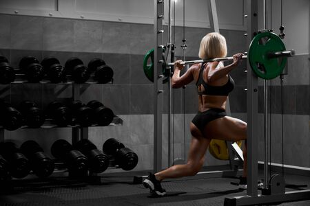 Side view of blonde female bodybuilder with short hair doing squats in multipower smith machine. Srtong woman with muscular body training legs in gym in dark atmosphere. Concept of bodybuilding. Stock Photo