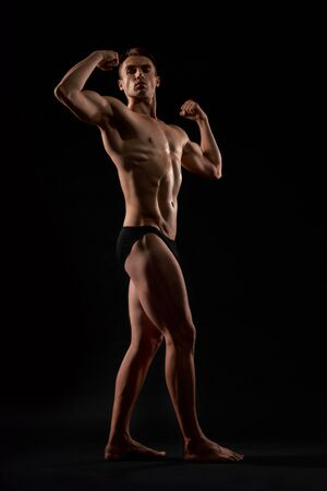 Side view of young fit bodybuilder with perfect body. Isolated portrait of pumped man demonstrating contest pose and looking away on black studio background. Contest of bodybuilding, sport. 写真素材