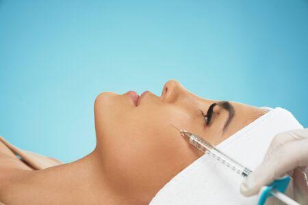 Cerca de la inyección de botox cosmético en la mejilla femenina. Cosmetóloga con jeringa con relleno mientras paciente joven bonita en toalla en la cabeza, aislado en azul. Concepto de cosmetología, belleza.
