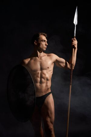 Front view of young athletic warrior with perfect body holding spear and shield. Crop of muscular bodubuilder posing with cold weapon on black studio background. Concept of warrior, strength.