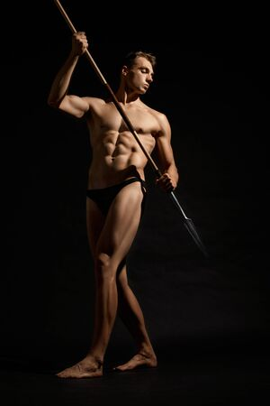 Side view of young athletic warrior with perfect body holding spear. Handsome bodubuilder posing with cold weapon and looking away on black studio background. Concept of warrior, strength. Stock fotó