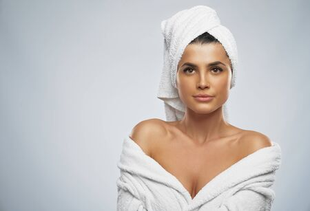 Front view of pretty female with towel on head and in bathrobe posing. Portrait of brunette woman with naked shoulders looking at camera, isolated on grey background. Beauty, skincare concept.