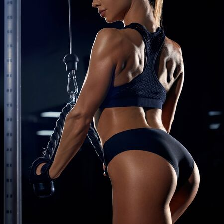 Back view of strong incognito fitness woman in black sportswear and gloves training triceps. Crop of female with perfect body building muscles with crossover. Concept of sport, bodybuilding. Imagens