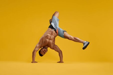Front view full length of athletic bodybuilder with perfect abs doing handstand exercise. Strong sporty guy standing upside down. Isolated on yellow studio background.