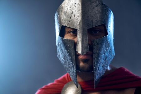 Portrait of spartan warrior standing and looking at camera. Close up of mature man in red cloak and helmet with water drops posing in dark atmosphere. Ancient sparta, warrior concept.