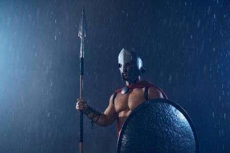 Portrait of spartan warrior standing outdoors with spear and shield in evening. Front view of muscular man in red cloak and helmet posing in bad cloudy rainy weather. Ancient sparta concept.