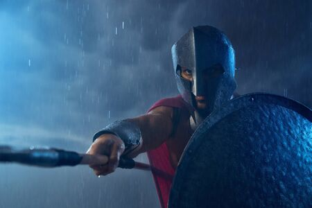 Portrait of muscular spartan in armor and red cloak fighting outdoors with spear. Front view of man in helmet holding shield and pointing weapon in bad cloudy rainy weather. Ancient sparta concept. 版權商用圖片