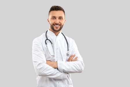 Front view of attractive confident brunette male doctor wearing lab coat and stethoscope, looking at camera with happy facial expression. Close up of intern isolated on grey. Concept of medicine. Stok Fotoğraf