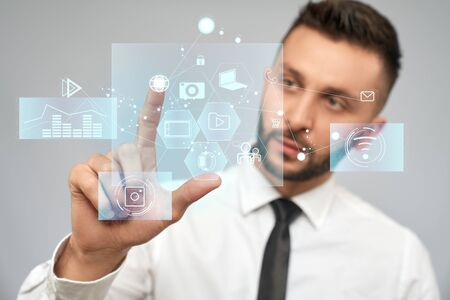 Close up of young serious businessman in white shirt in office. Selective focus of digital tactile charts screen, bearded man clicking virtual icon. Concept of high technologies, digitalization.