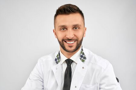 Front view of handsome confident brunette male doctor wearing lab coat and looking at camera with happy expression. Close up of bearded medic sitting, isolated on grey. Concept of medicine. Stok Fotoğraf