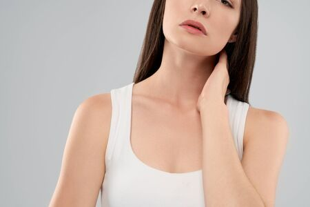 Clolse up of incognito caucasian woman in white shirt posing over gray isolated background and touching neck with hand because of ache. Front crop of brunette breathing with mouth.