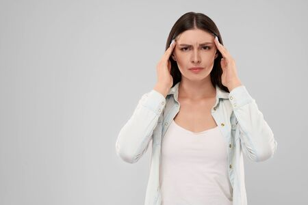 Young caucasian woman in white shirt over gray isolated background touching head with two hands with painful expression because of migraine. Front view of brunette looking at camera. Banco de Imagens
