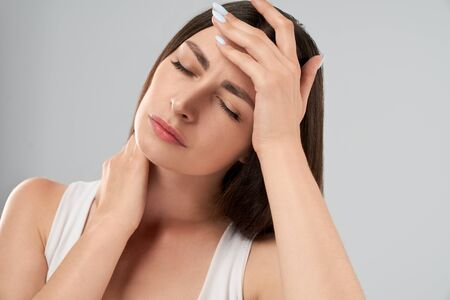 Clolse up of pretty caucasian woman in white shirt posing over gray isolated background and touching head with hand because of migraine. Front crop of brunette suffering from pain.