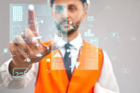 Close up of architect wearing reflective vest and helmet. Selective focus of digital tactile charts screen, man touching virtual icon on projection. Concept of digitalization, construction. Stock Photo