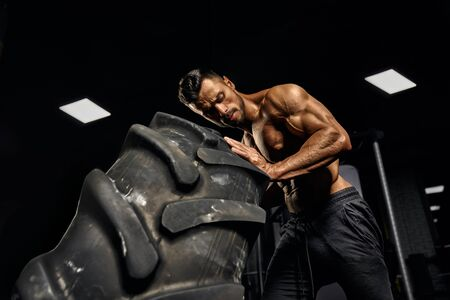 Close up of fit young shirtless man moving giant black tire in gym. From below view of strong attractive muscular male athlete pushing large wheel in dark atmosphere. Concept of bodybuilding, workout.