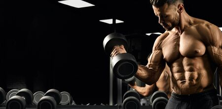 Cropof shirtless bodybuilder training biceps with dumbbell. Close up of muscular sportsman with perfect tensed muscular body posing in gym in dark atmosphere. Concept of bodybuilding. Stok Fotoğraf