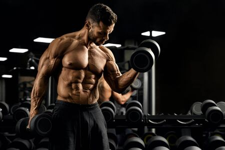 Front view of shirtless bodybuilder training biceps with dumbbell near mirror. Close up of muscular sportsman with perfect body posing in gym in dark atmosphere. Concept of bodybuilding.