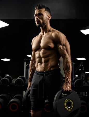 Side view of shirtless tensed male bodybuilder holding weights in arms. Close up portrait of caucasian sportsman with perfect muscular body posing in gym in dark atmosphere. Concept of bodybuilding.