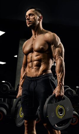 From below view of shirtless male bodybuilder holding weights in arms. Close up portrait of caucasian sportsman with perfect muscular body posing in gym in dark atmosphere. Concept of bodybuilding.