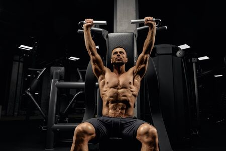 From below view of handsome muscular man sitting on simulator in empty gym. Portrait of shirtless bodybuilder with perfect tensed body training back and looking up. Concept of sport.