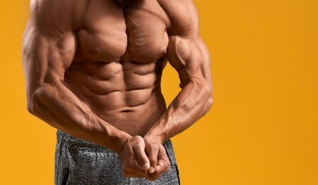 Close up of strong bodybuilder demonstrating muscular arms and perfect six-pack abs. Shirtless guy showing results of workout in gym and diet. Isolated on yellow studio background. Stock Photo