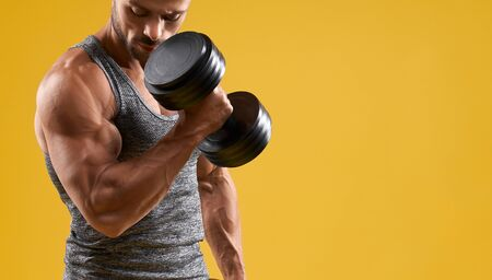 Close up of athletic young man lifting heavy weight. Muscular gentleman pumping up biceps. Isolated on yellow studio background with copy space. Concept of sport and bodybuilding.