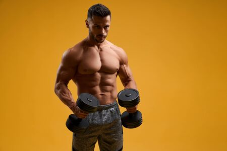 Front view of muscular young man with perfect abs working out with dumbbells. Shirtless bodybuilder looking aside with serious expression. Isolated on yellow studio background.