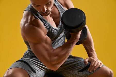 Close up of strong athletic man doing exercise with dumbbell. Handsome brutal bodybuilder lifting heavy weight. Isolated on yellow studio background. Concept of sport and muscle pump.