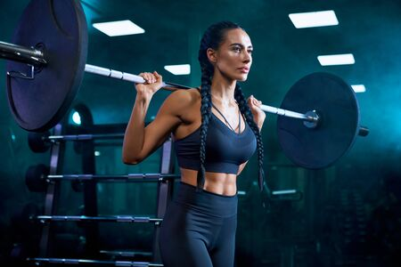 Side crop of brunette female bodybuilder with long braids doing squats using barbell on shoulders. Srtong woman with muscular body training in gym in dark atmosphere. Concept of bodybuilding.